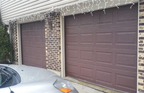 two brown garage doors on brick garage before