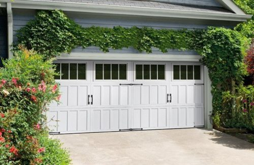White double garage doors surrounded by ivy