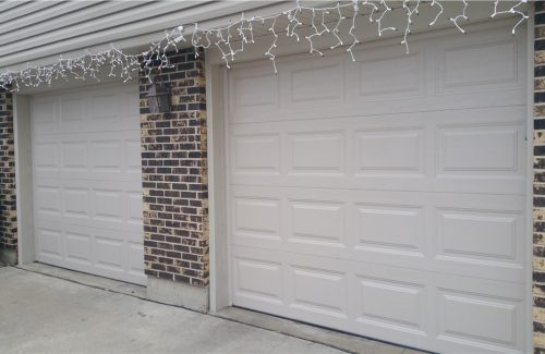 two white garage doors on brick garage after