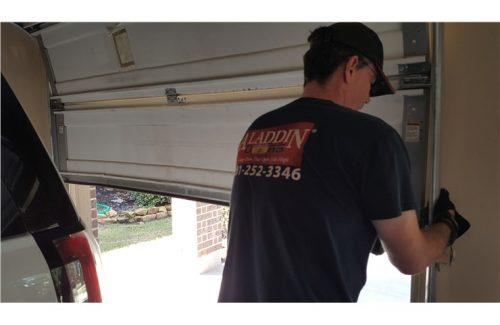 man putting garage door back on track