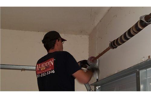 man fixing garage door spring
