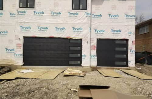 black garage doors on house under construction