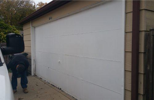 white garage door on tan garage before