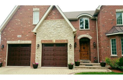 brown wooden garage doors on large brick house