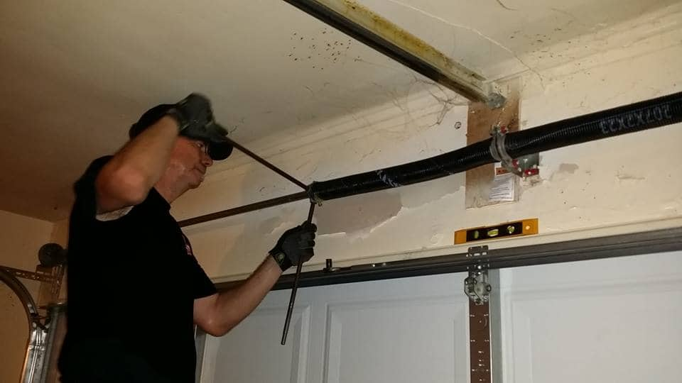 man replacing springs on garage door