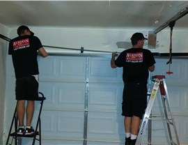 two aladdin employees installing garage door